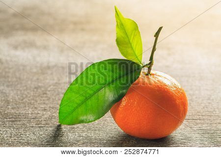 Single Mandarin In Juicy Orange Colour With Green Leaf On Vintage Wooden Table. Horizontal Orientati
