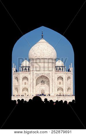 Taj Mahal In India. Popular Tourist Destination. Arch View With Tourists In Front.