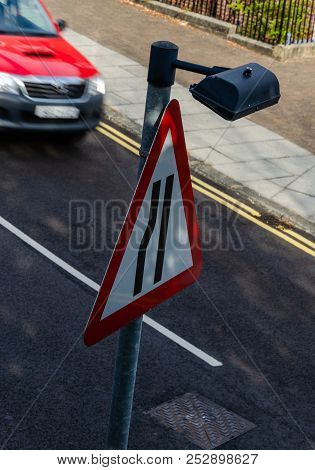 An Unusual View From Above Of A British Road Sign Which Informs Drivers That The Left Lane Narrows A