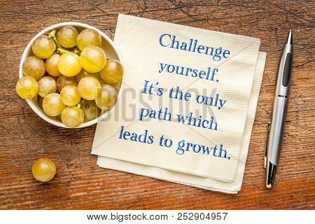 Challenge yourself, it is the only path which leads to growth - inspirational handwriting on a napkin with fresh grapes.