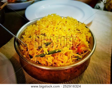 Handi Biryni Sweet Pulao Rice Dish Indian Cuisine In A Bowl On A Table With White Plates