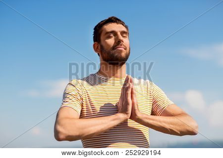 meditation, spirituality and mindfulness concept - man meditating outdoors over sky