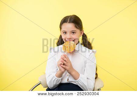Lollipop Child. Child Eating Lollipop In Yellow Studio. Lollipop Child Eating Candy With Happy Face.