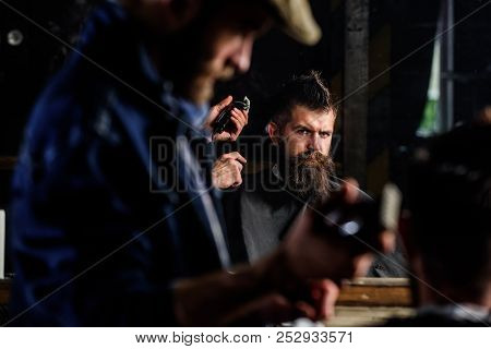 Barber With Hair Clipper Works On Hairstyle For Man With Beard, Barbershop Background. Haircut Conce