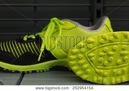 Modern Sports Shoes In  Black  And Yellow-green Vibrant Color On The Gray Background