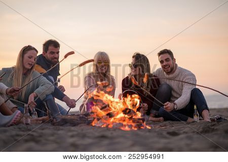 Group of young friends sitting by the fire at autumn beach, grilling sausages and drinking beer, talking and having fun