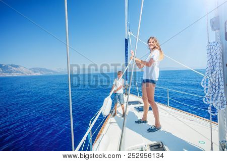 Girl With Her Brother On Board Of Sailing Yacht On Summer Cruise. Travel Adventure, Yachting With Ch