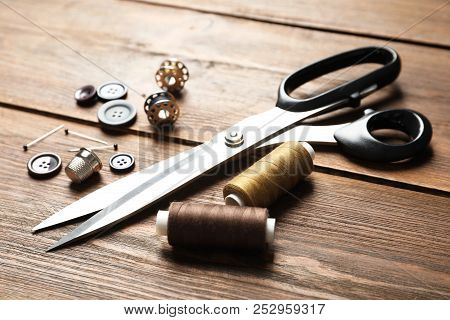 Set Of Tailoring Accessories On Wooden Background