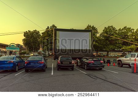 Spectators At A Car Parking Lot With Cars, An Inflatable Screen Of The Summer Cinema, Waiting For A