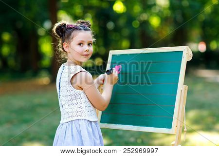 Happy Little Kid Girl Standing By Big Chalk Desk Preschool Or Schoolkid On First Day Of Elementary C
