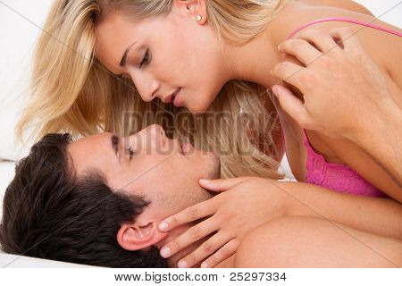 couple in bed during sex and tenderness.