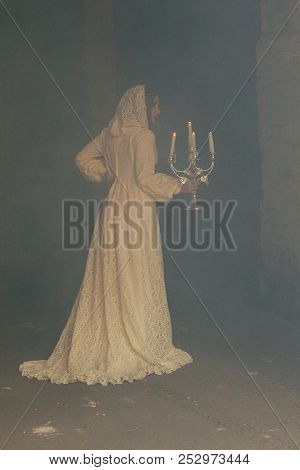 Mysterious Woman In Long Dress With Candles