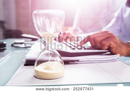 Hourglass In Front Of Businessperson Calculating Invoice