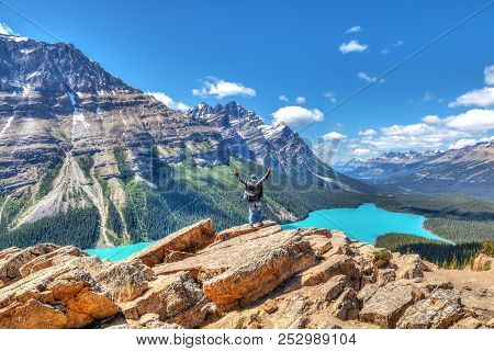 A Hiker Stands In Awe On Top Of Bow Summit Overlooking Peyto Lake In Banff National Park On The Icef