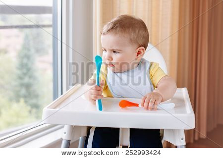 Portrait of cute adorable Caucasian child boy sitting in high chair with spoons. Everyday home childhood lifestyle. Infant trying supplementary baby food poster