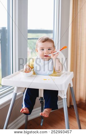 Portrait of cute adorable Caucasian child boy with dirty messy face sitting in high chair eating apple puree with spoon. Everyday home childhood lifestyle. Infant trying supplementary baby food poster