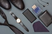 Black necktie, men's shoes, watch with leather strap, mobile phone, handkerchief, leather purse, cologne for men and headphones on grey background. Accessories for men. Top view poster