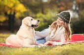 Girl playing with a labrador retriever dog in the park poster
