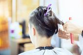 Beauty, hairstyle, treatment, hair care concept, young woman and hairdresser cutting hair at hairdressing salon. Hairdresser cuts girl's hair. Hairstylist serving client at barber shop poster