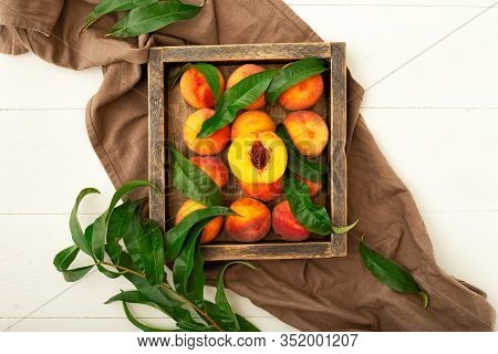 Peaches With Leaves In A Wooden Box. Flat Lay Composition With Ripe Juicy Peaches On A White Backgro