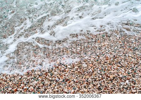 Washed By A Wave Of Colorful Pebbles On The Beach Of The Adriatic Sea. Sea Foam, Clear Sea Water And