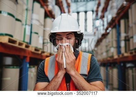 Young Warehouse Manager Coughing And Sneezing While Feeling Sick And Covering Mouth With Handkerchie