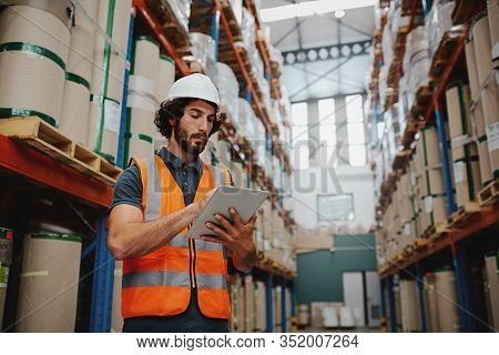 Young Caucasian Engineer In Hardhat Is Using A Tablet Computer In A Heavy Industry Factory Wearing W