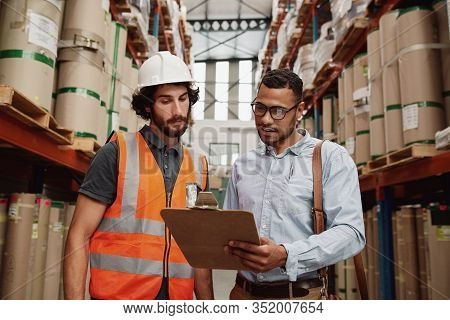 Portrait Of Warehouse Owner Talking To Friendly Young Banker - Warehouse Manager Wearing Formal Clot