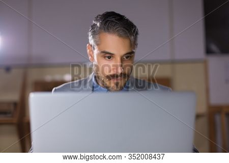 Front View Of Focused Man Looking At Laptop. Concentrated Handsome Manager Sitting At Table And Work