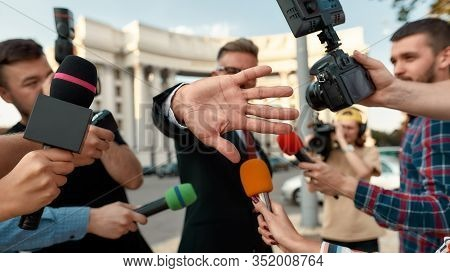 Horizontal Shot Of Politician Trying To Cover Camera Lens With His Hand While Refusing To Give Inter