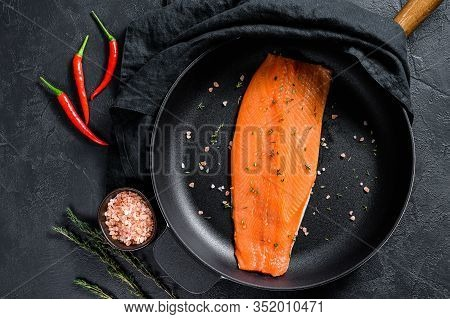 Raw Salmon Fillet With Salt And Chili Pepper In A Pan. Organic Fish. Black Background. Top View