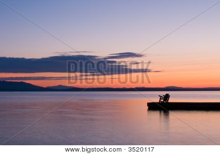 Empty Chair At The End Of Wooden Pier On Lake At Sunset