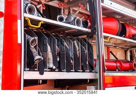 Rescue Fire Truck Equipment. Compartment Of The Rolled Up Fire Hoses On A Fire Engine