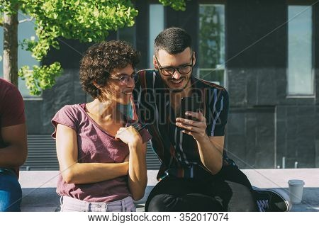 Cheerful Geek Couple Discussing Online Mobile App. Man And Woman In Glasses Sitting On Parapet Outsi