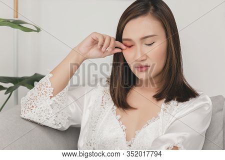 A Girl Scratch Because Of Rubbing On The Right Eyelid. Woman Wears A White Nightgown And Long Sleeve