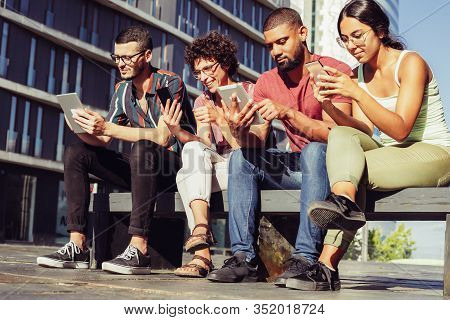 Group Portrait Of Young People Focused On Their Digital Gadgets. Men And Women Sitting On Bench Outs