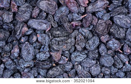 Black Raisins Texture Background. Sweet Dried Fruit. Blue Grape Raisins
