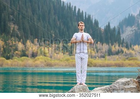 A Young Man In White Practices Yoga In The Mountains. Pose Samasthiti Namaskar