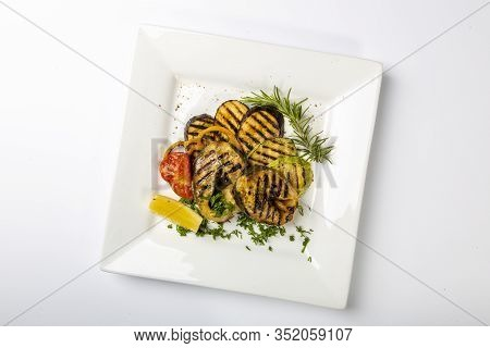 Sturgeon Steak On The Grill. A Few Pieces Of Grilled Sturgeon Steak Lie On A Square Plate. Sprinkled