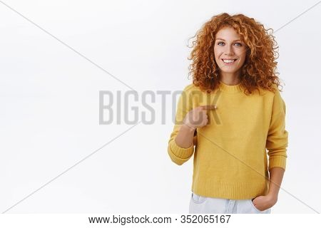 Silly Attractive Redhead Curly Woman In Yellow Sweater, Pointing Herself And Smiling, Express Person