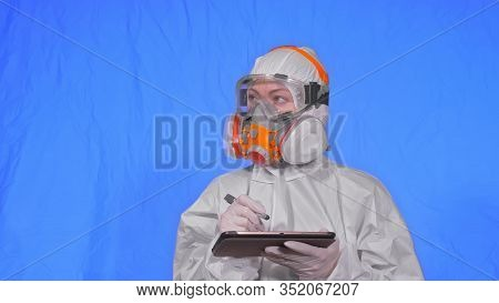 Scientist Virologist In Respirator Makes Write In An Tablet Computer With Stylus. Woman Wearing Prot