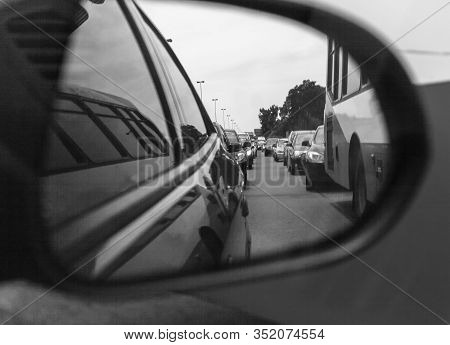 Reflection Of A Traffic Jam In A Sideview Mirror. Old Black And White Photography Filter Applied