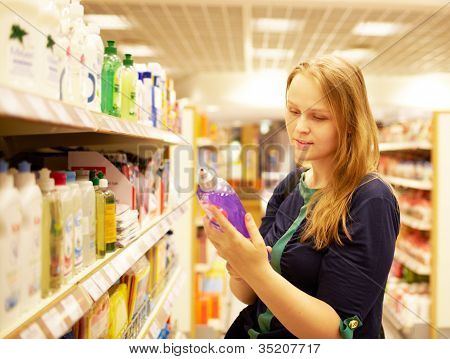 Young woman in the supermarket reading inscription