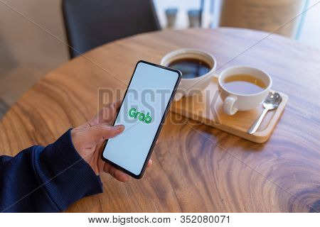 Chiang Mai, Thailand - Jan.18,2020: Man Holding Xiaomi Mi Mix 3 With Grab Apps On Screen. Grab Is Sm