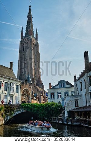 BRUGES, BELGIUM - MAY 28, 2018: Tourist boat with tourists in canal near Church of Our Lady . Brugge Bruges, Belgium