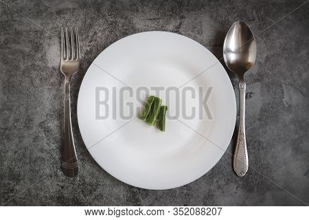 A Round White Plate With Some Food And A Metal Fork With A Spoon On A Gray Cement Background. The Co