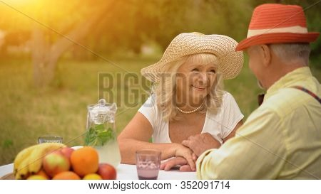 Good-looking Middle-aged Lady In A Cute Straw Hat Is Looking At Her Husband.the Gentleman Is Looking