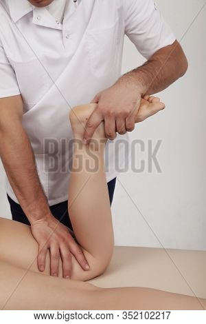 Osteopath Does Massage Of Feet And Legs To A Girl On A White Background