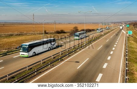Caravan Or Convoy Of Four White Buses In Line Traveling On A Country Highway Under Amazing Blue Sky.