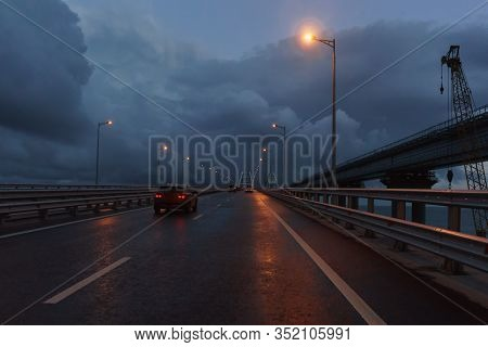 Cars Drive On The Crimean Bridge In The Late Evening. Dull